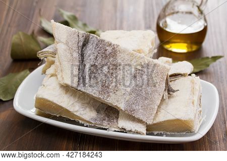 Salted Raw Dry Cod Fish On Dish On Wooden Background