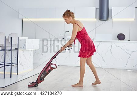 Slender Woman In Nightgown Vacuums Floor With Cordless Vacuum Cleaner.