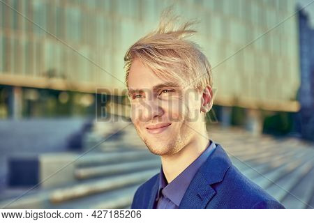 Smiling White Collar Worker 25 Years Old In Business Suit In Front Of An Office Building.