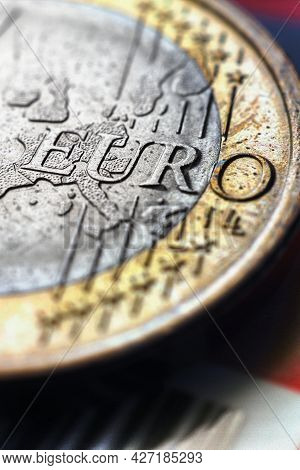 1 One Euro Coin Lies On A Bank Plastic Card. Focus On The Name Of The Eurozone Currency. Vertical Il