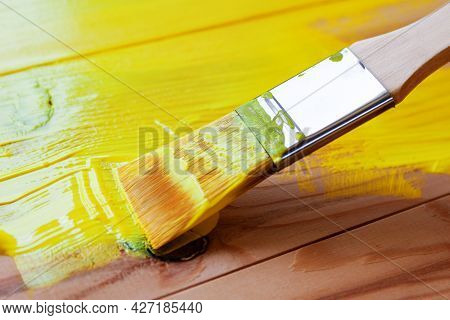 Painting The Surface Of The Board With A Brush With Synthetic Bristles With Acrylic Yellow Paint
