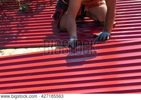 A Man Screws Sheets Of Corrugated Board On The Roof With A Screwdriver. Repair And Replacement Of Th