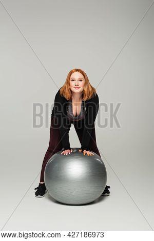 Plus Size Sportswoman Standing Near Fitness Ball On Grey Background