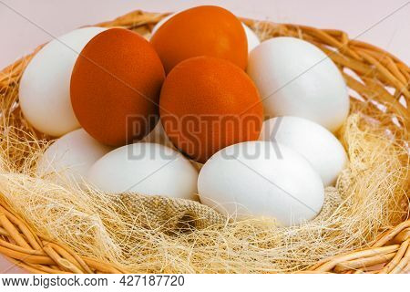 This Is A Rustic Wicker Basket With Natural White And Brown Chicken Eggs. Simple Authentic Photo Of
