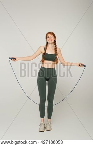 Smiling Freckled Sportswoman Holding Jump Rope On Grey Background