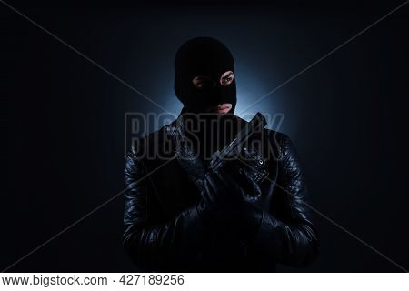 Man Wearing Knitted Balaclava With Gun On Black Background
