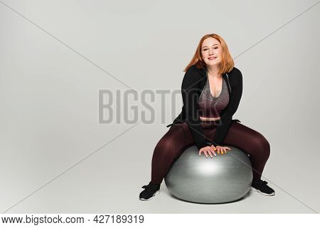 Cheerful Plus Size Sportswoman Sitting On Fitness Ball On Grey Background