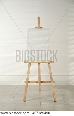 Wooden Easel With Blank Canvas Near Light Wall