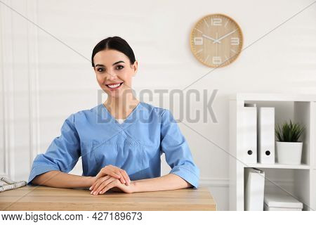 Portrait Of Receptionist At Countertop In Hospital