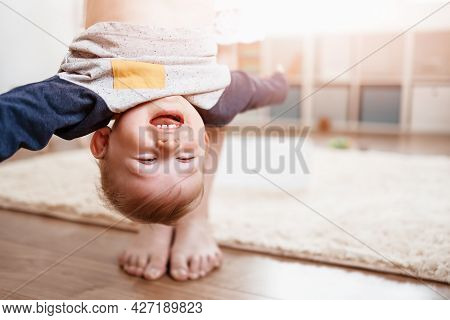Mother Holding Upside Down Her Laughing Child.