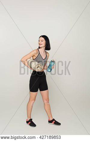Cheerful Sportswoman With Vitiligo Holding Sports Bottle And Fitness Mat On Grey Background