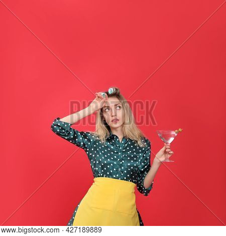 Young Housewife With Glass Of Martini On Red Background
