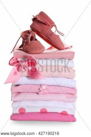 Stack Of Clean Girl's Clothes With Booties And Bow On White Background