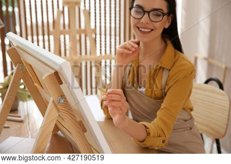 Young Woman Drawing On Easel With Pencil At Table Indoors