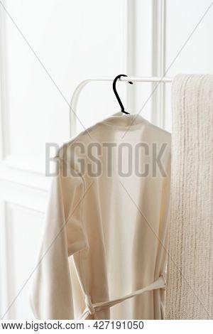 White bathrobe hanging on a clothing rack