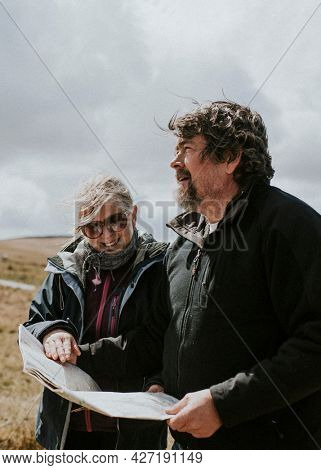 Senior tourist couple looking at the map while being lost in Wales, UK