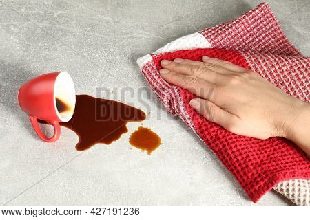 Woman Wiping Spilled Coffee On Grey Table, Closeup