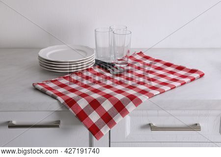 Dry Kitchen Towel And Clean Dishware On White Marble Countertop