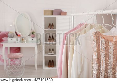 Different Clothes On Rack In Stylish Dressing Room, Space For Text. Interior Design