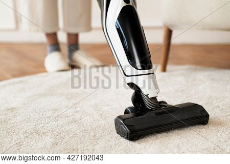 Vacuum cleaning a rug on the floor