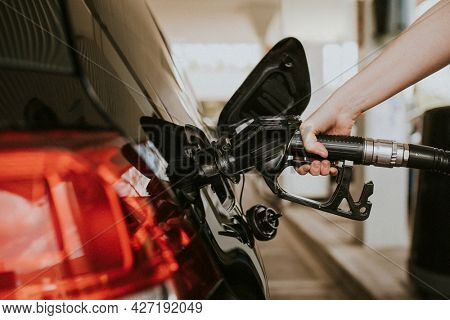 Woman filling petrol at a gas station
