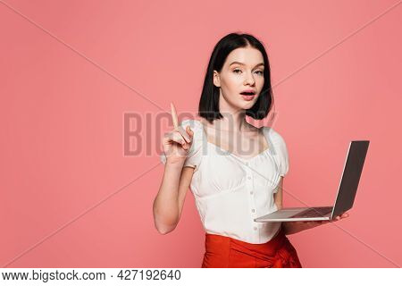 Astonished Woman With Vitiligo Holding Laptop And Showing Idea Gesture Isolated On Pink