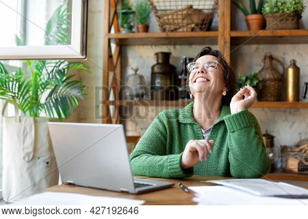 Happy Laughing Senior Woman In Front Of Laptop Monitor. She Sitting In Home Interior And Having Onli