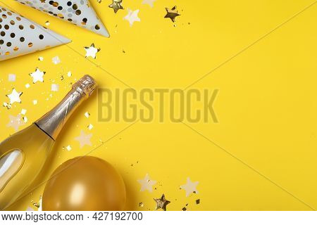 Flat Lay Composition With Birthday Decor And Bottle Of Sparkling Wine On Yellow Background, Space Fo