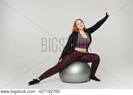 Plus Size Sportswoman Exercising On Fitness Ball On Grey Background