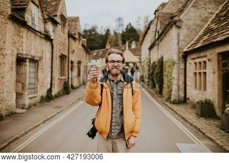 Tourist holding coffee cup smiling in the village