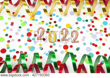 Celebrating New Year 2022, Colorful Photo Of The Numbers 2022 With Paper Streamers And Confetti On W