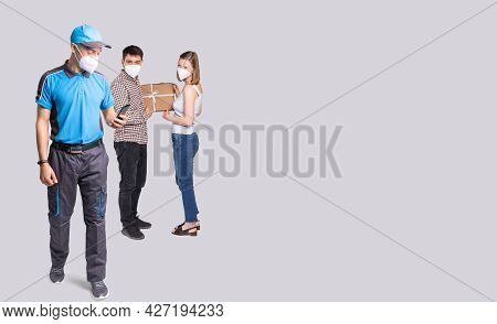 Courier With The Mobile Phone In The Hand Delivered A Box During A Pandemic Time So They Are Wearing