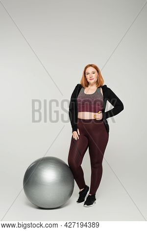 Plus Size Sportswoman Holding Hand On Hip Near Fitness Ball On Grey Background