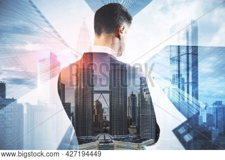 Back View Of Young Businessperson Standing On Abstract City Background With Mock Up Place. Success A