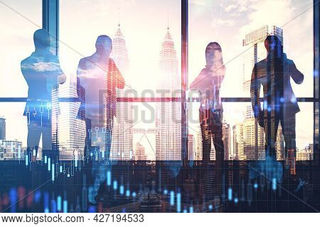 Businesspeople Standing On Abstract Illuminated City Background With Forex Chart. Teamwork And Finan