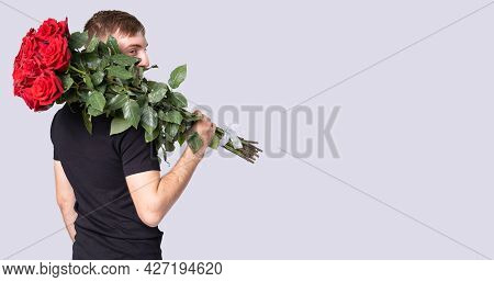 One Courier Man In A Black Shirt Delivers A Beautiful Bouquet Of Red Roses And Holds It On His Right