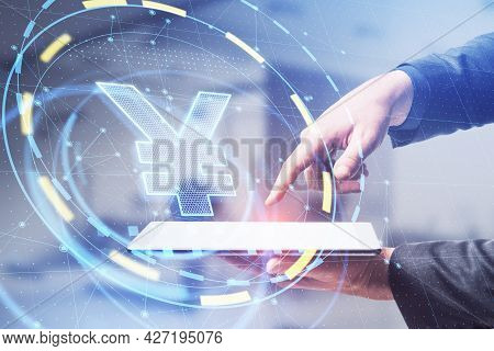 Side View Of Businessman Hands Using Tablet With Glowing Yen Hologram In Blurry Office Interior. Cur