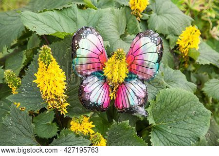 A Bright Artificial Butterfly Made Up Of An Inflatable Ball And A Green Flower On A Green Background