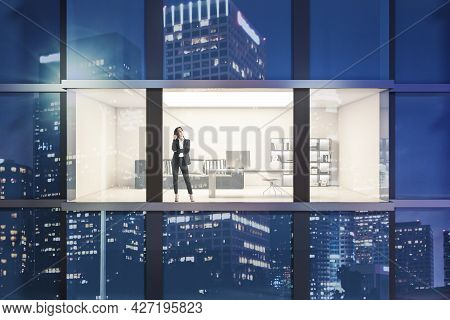 Creative Night Time Glass Building Exterior With Window And Thoughtful Young Businesswoman In Office