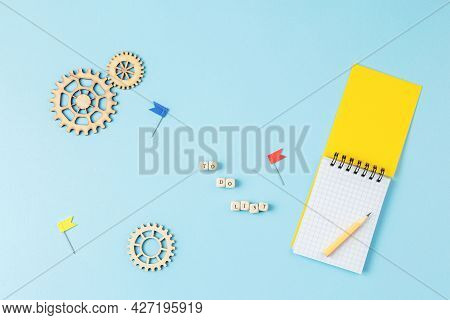 Inscription To Do List Is Stacked Of Wooden Cubes, Yellow Notebook With A Pencil, Stationery Pins In