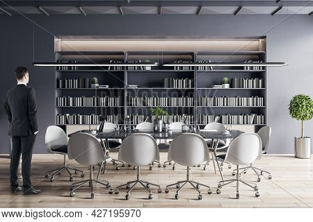 Businessman Standing In Modern Meeting Room Interior With Furniture, Bookcase. Corporate Workplace A
