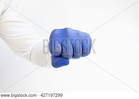 Hand , Fist In Blue Latex Glove Ready To Punch. White Background. Copy Space