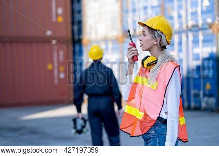 Foreman Or Cargo Container Woman Worker Use Walkie Talkie To Communicate With Her Team And Co-worker