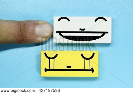 Fingers Pushed Away Happy Faces And Left Sad Faces. The Concept Of Sad And Happy