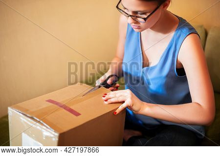 Caucasian Female Customer Unpacking Carton Post Parcel With Scissor, Satisfied With Good Online Shop