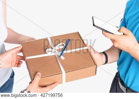 The Courier In A Blue Uniform Marks In His Mobile Phone The Parcel Was Delivered On Time For A Young