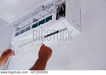 Air Conditioner Repair And Maintenance. A Man Holds An Air Conditioner Filter In His Hands