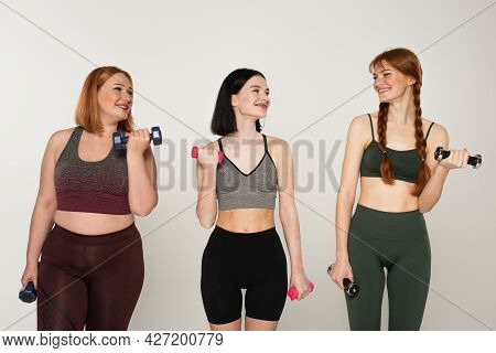 Sportswomen Training With Dumbbells And Looking At Freckled Friend Isolated On Grey