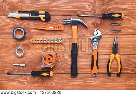 Set Of Construction Tools On A Wooden Background. Hammer, Wrench, Pliers And Screwdriver. Gift Card