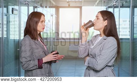 Ladies Company Managers With Loose Dark Hair Talk And Drink Coffee From Black Plastic Cups In Hall A